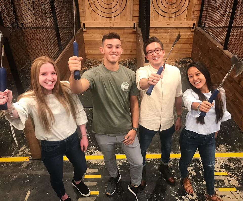 Two men and two women raise their axes and smile while axe throwing