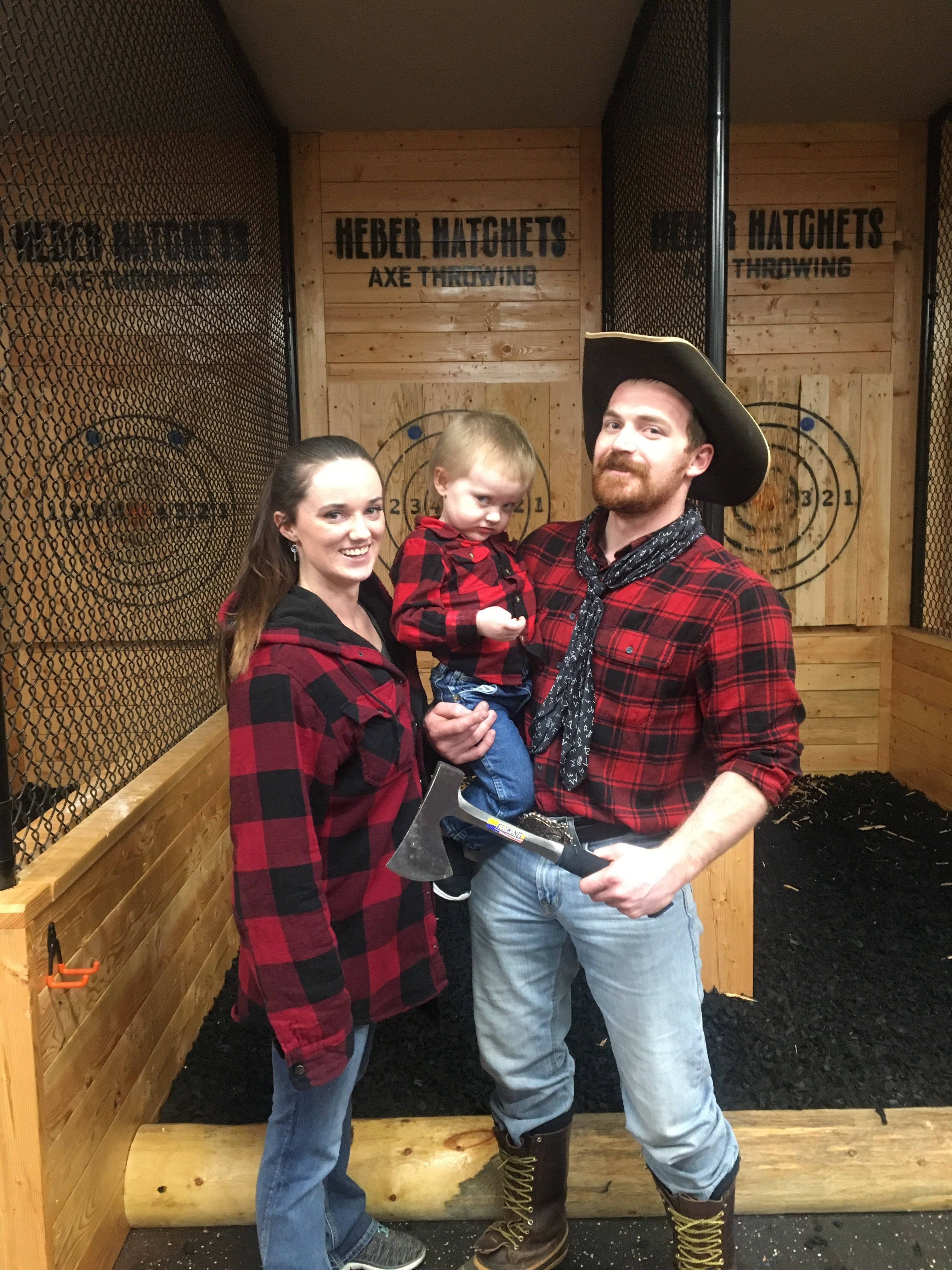 A family wearing flannel poses with an axe at Heber Hatchets in Rexburg