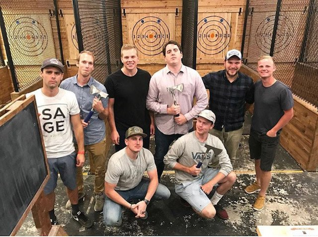 a group of men pose with axes during a bachelor party