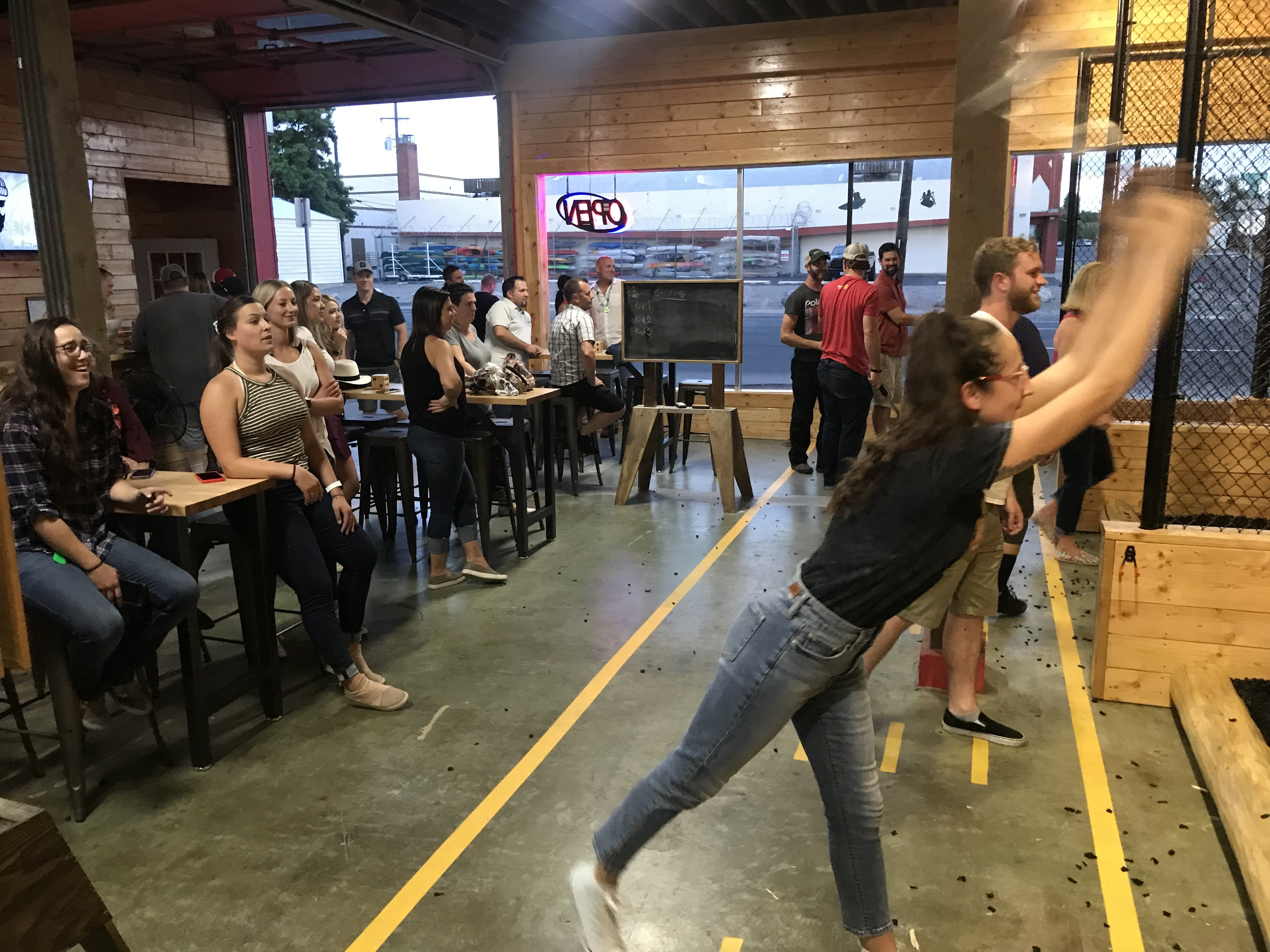 a large group enjoys axe throwing games at Heber Hatchets in Spokane